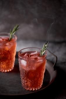 Zbliżenie strzał czerwonych napojów alkoholowych z liśćmi rozmarynu na tacy