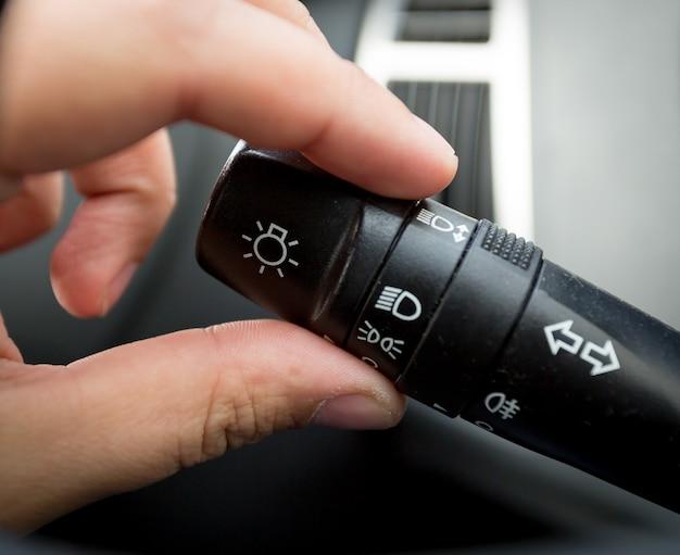 Zbliżenie strzał człowieka dostosowujący przełącznik sterowania światłem w samochodzie