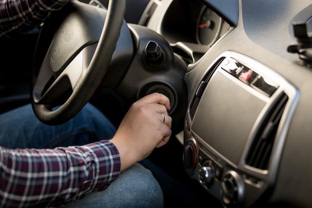 Zbliżenie strzał człowieka wkładając klucz w stacyjka samochodu car