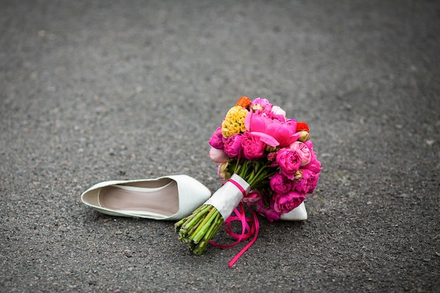 Zbliżenie strzał eleganccy biali ślubów buty i świeży bukiet