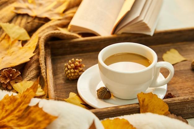 Zbliżenie strzał filiżanki kawy i jesiennych liści na drewnianej powierzchni