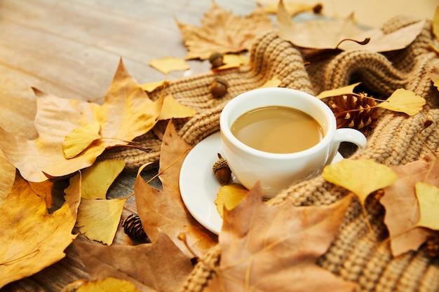 Zbliżenie strzał filiżanki kawy i jesiennych liści na drewnianym tle