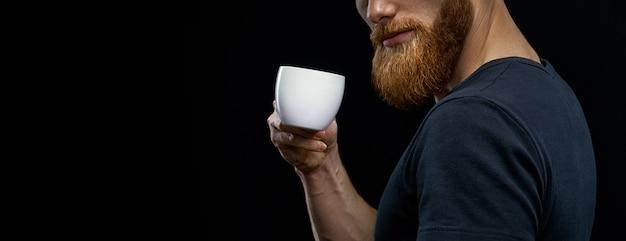 Zbliżenie strzał filiżanki kawy. piękny młody brodaty mężczyzna picia kawy. odpoczynek brodaty mężczyzna pijący kawę espresso trzymając w ręku filiżankę kawy studio strzał na czarnym tle