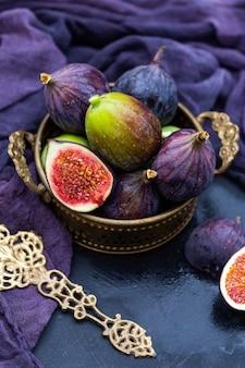 Zbliżenie strzał fioletowej i zielonej świeżej figi w koszu