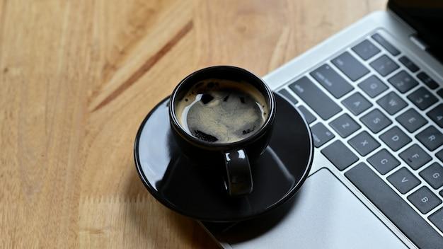 Zbliżenie strzał gorącej kawy umieszczone na klawiaturze laptopa na drewnianym stole.