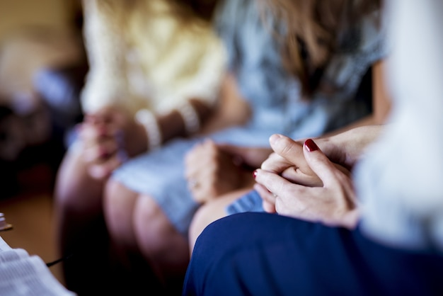 Zbliżenie strzał kobiet siedzących trzymając się za ręce i modląc się