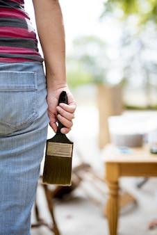 Zbliżenie strzał kobieta trzyma dużego paintbrush z zamazanym tłem