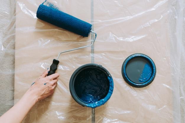 Zbliżenie strzał kobieta używa farba rolowników z koloru błękitem
