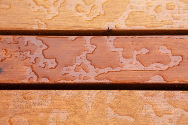 Zbliżenie strzał kropli deszczu na drewnianej ławce