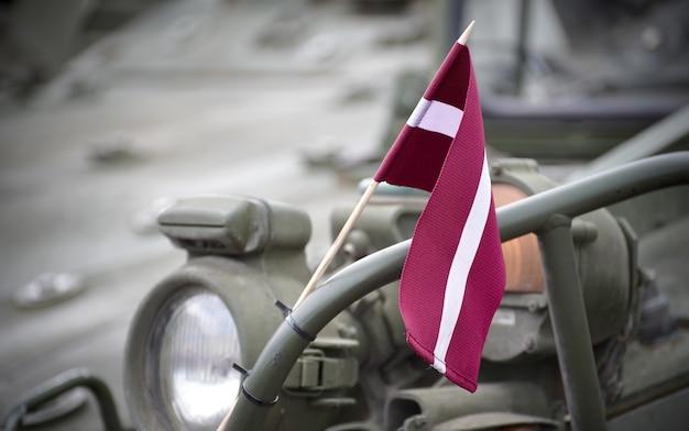 Zbliżenie strzał małej łotewskiej flagi na metalowej balustradzie