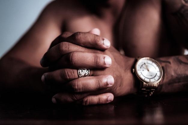 Zbliżenie strzał męskich rąk z pierścionkiem i zegarkiem