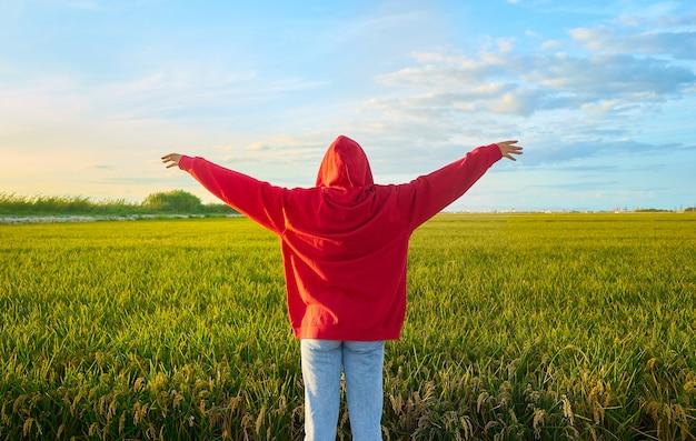 Zbliżenie strzał młodej damy w czerwieni wesoło stojącej w zielonym polu w słoneczny dzień
