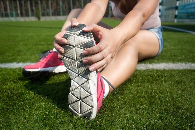 Zbliżenie strzał młodej kobiety rozgrzewa się na trawie przed uruchomieniem