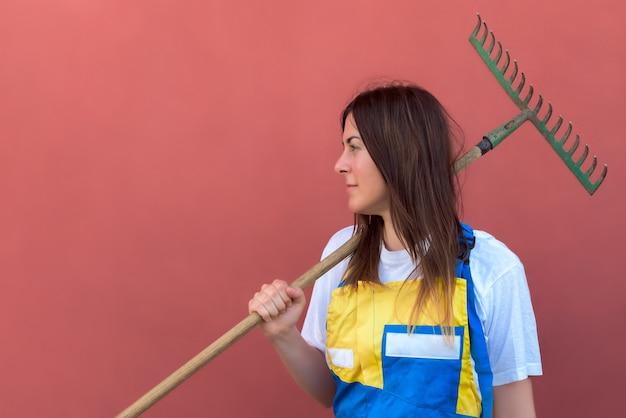 Zbliżenie strzał młodej kobiety z narzędziem grabienia trawy