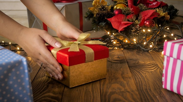 Zbliżenie strzał młodej matki oddanie prezentu dla jej dziecka pod choinką