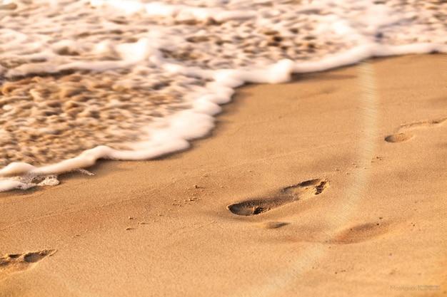 Zbliżenie strzał odciski stopy w piaskowatej powierzchni blisko plaży przy dniem