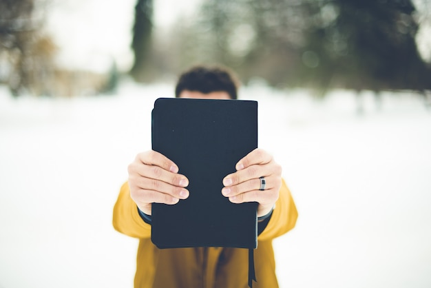 Zbliżenie strzał samiec trzyma biblię
