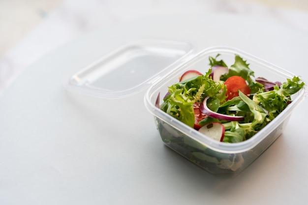 Zbliżenie strzał świeżej sałatki w plastikowym pudełku na białej powierzchni