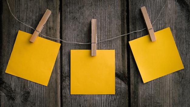 Zbliżenie strzał wiszącego żółtego papieru na drewnianym klipsie