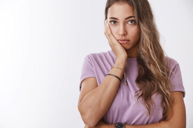 Zbliżenie strzał znudzony podrażniony atrakcyjna młoda kobieta dosyć walki z trądzikiem zły stan skóry pochylony dłoń twarz patrząc ponury obojętny dąsanie się stojący samotny smutny biała ściana