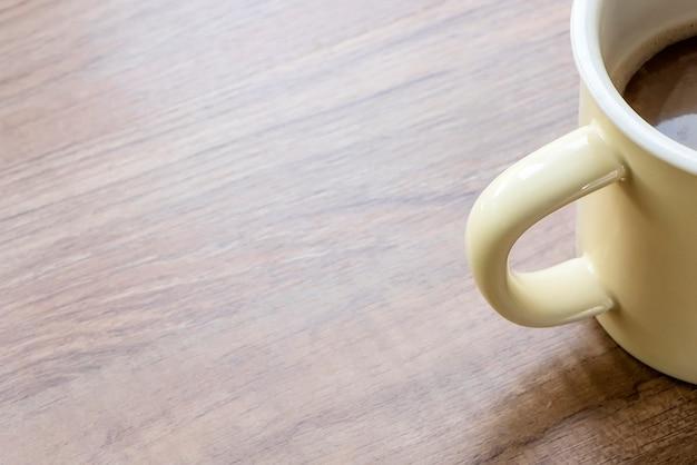 Zbliżenie strzał żółta filiżanka kawy na drewnianym stole z kopii przestrzenią.