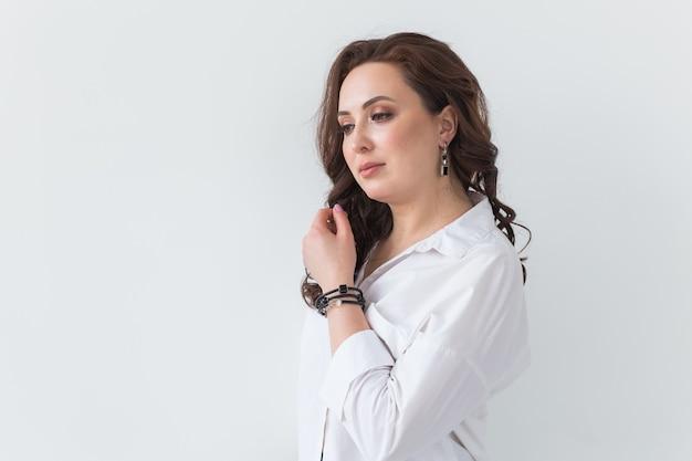 Zbliżenie: strzelać moda młoda brunetka kobieta z elegancką fryzurą w białym studio. koncepcja modnego stylu. skopiuj miejsce.