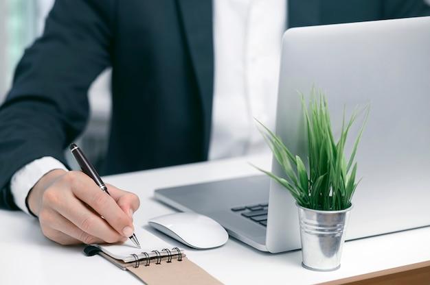 Zbliżenie strzelał biznesmena używa pióra writing na notatniku podczas gdy pracujący z laptopem przy nowożytnym biurem.