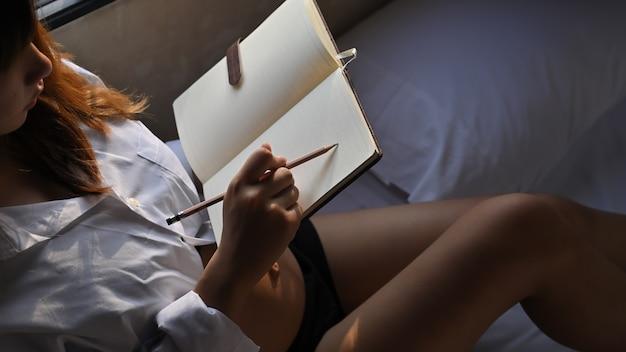 Zbliżenie strzelał ciężarnego żeńskiego writing na notatniku w rekreacyjnym pojeździe.