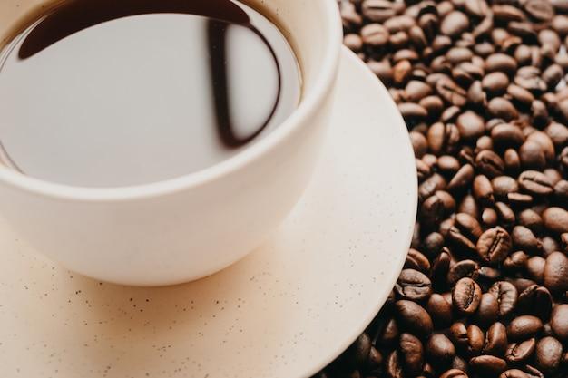 Zbliżenie strzelał filiżanka kawy z kawowymi fasolami na bielu