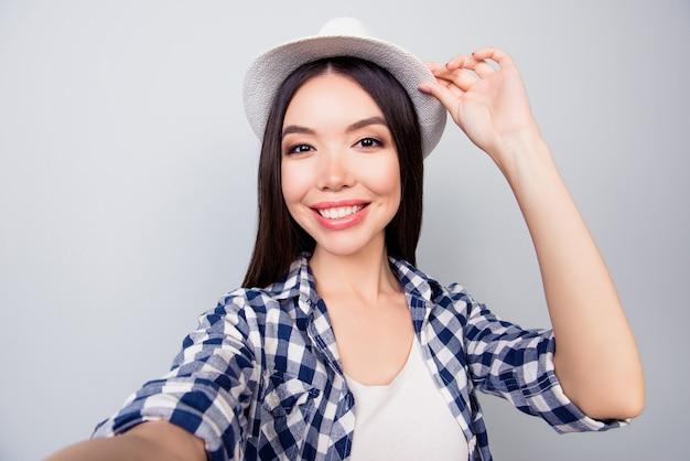Zbliżenie studenta biorąc autoportret dotykając jej czapkę