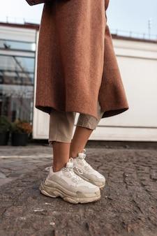 Zbliżenie stylowe kobiece nogi w beżowe spodnie w modne skórzane trampki. nowoczesna dziewczyna w długim płaszczu w butach młodzieżowych stoi na kamiennej drodze w mieście. nowa kolekcja butów damskich. wiosenny styl casual.
