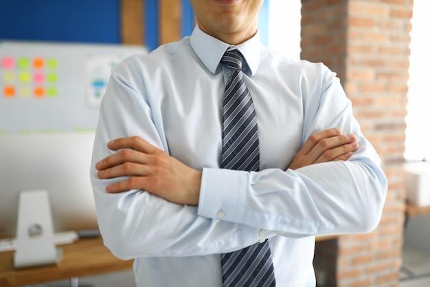 Zbliżenie: stylowy biznesmen stojący ze skrzyżowanymi rękami w osobistym gabinecie. profesjonalny specjalista od modnych kostiumów. człowiek sukcesu. projektowanie wnętrz i koncepcja biznesowa