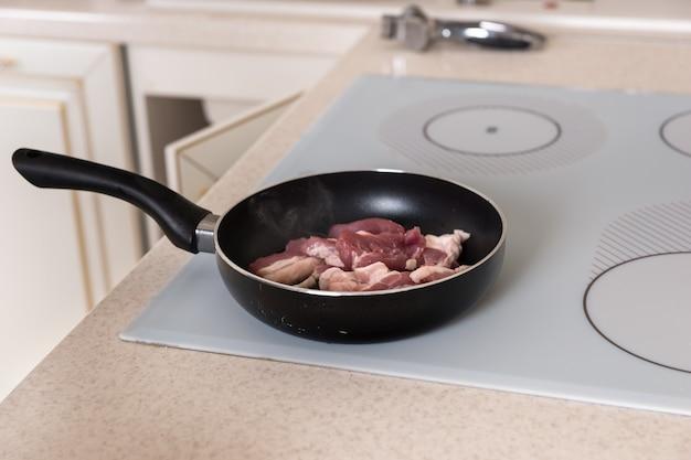 Zbliżenie surowego mięsa pokrojonego w plasterki gotowania na patelni na płaskiej płycie kuchennej w domowej kuchni