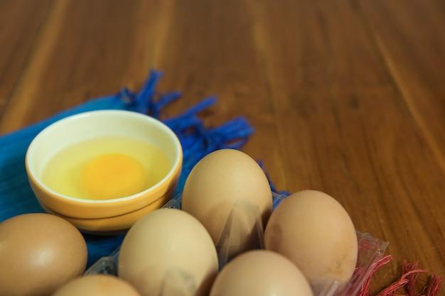 Zbliżenie surowych jaj kurzych w pudełku na jajka na żółtym tle drewnianych.