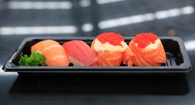 Zbliżenie sushi owoce morza na czarnej tacy na czarnym stole. kuchnia japońska?