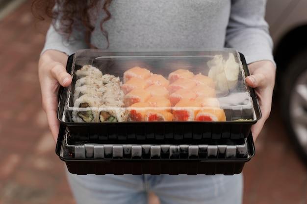 Zbliżenie sushi w polu usługi online dostawy zdrowej żywności. dziewczyna trzyma w rękach 2 zestawy sushi. bułki kuchni japońskiej, sos sojowy, wasabi.