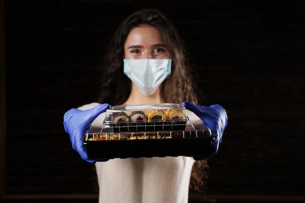 Zbliżenie sushi w polu usługi online dostawy zdrowej żywności. dziewczyna trzyma w rękach 2 zestawy sushi. kuchnia japońska: bułki, sos sojowy, wasabi