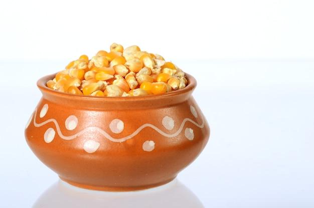 Zbliżenie suszonej kukurydzy w glinianym garnku