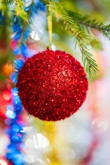 Zbliżenie świątecznej ozdoby na obchody szczęśliwego nowego roku lśniąca czerwona piłka wisząca na gałęzi sosny