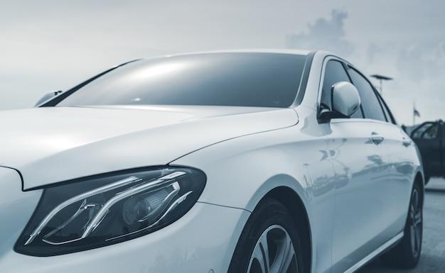 Zbliżenie światła reflektorów białego samochodu. biały luksusowy samochód zaparkowany na odkrytym parkingu. koncepcja przemysłu motoryzacyjnego. koncepcja pojazdu elektrycznego. serwis samochodowy. podróż w podróż. wynajem samochodu.