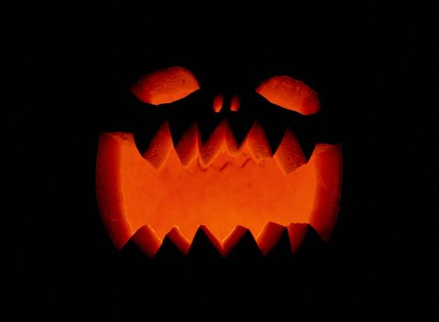 Zbliżenie światła wpadającego przez rzeźbioną dynię na halloween w ciemnym otoczeniu