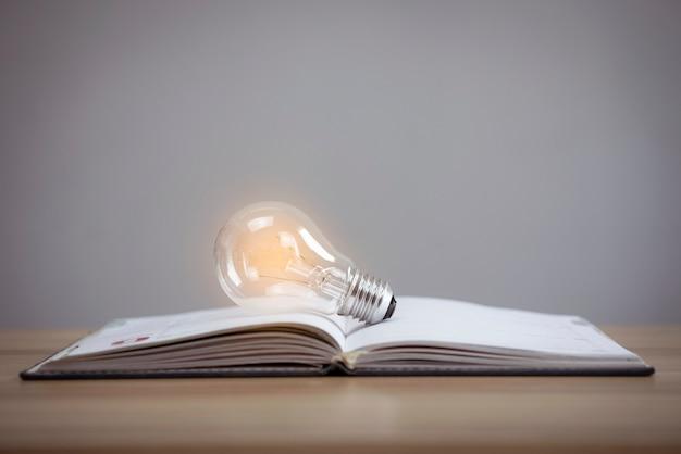 Zbliżenie świecąca żarówka i książka na tle stołu