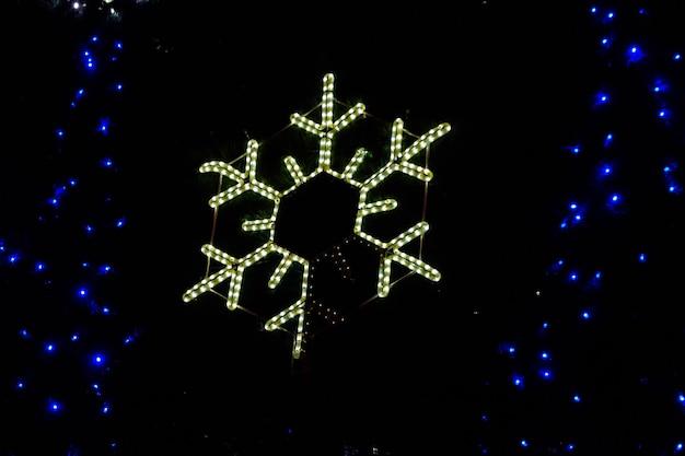 Zbliżenie świecącego płatka śniegu na choince w nocy
