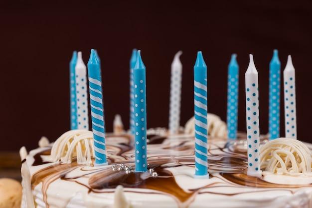 Zbliżenie świeczek urodzinowych na białym domowym cieście, na drewnianym biurku