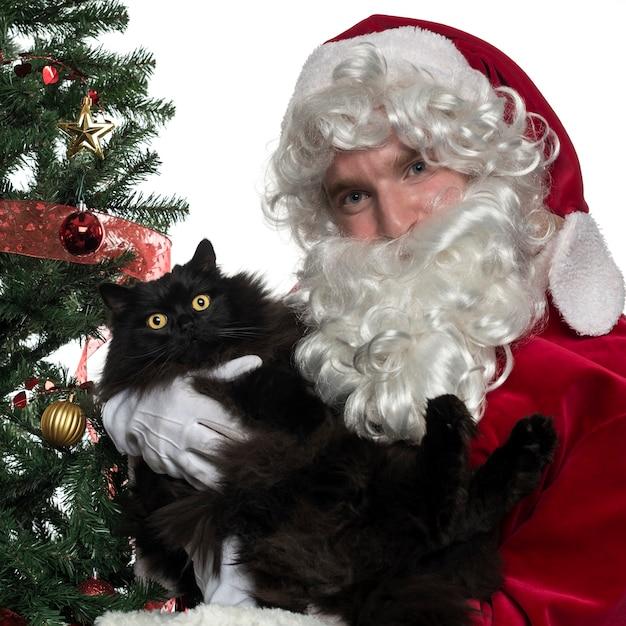 Zbliżenie: święty mikołaj trzyma czarnego kota na białym tle