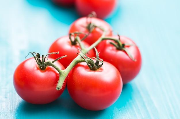 Zbliżenie: świeże dojrzałe pomidory czereśniowe na turkusowym drewnianym stole