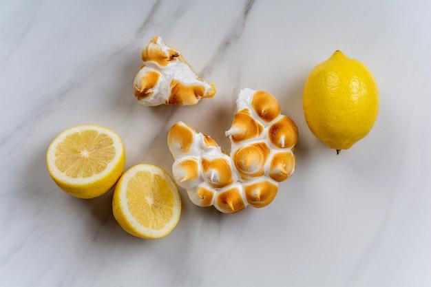 Zbliżenie: świeże domowe ciasto cytrynowe z bezą i cytryną z owoców cytrusowych. koncepcja piekarni.