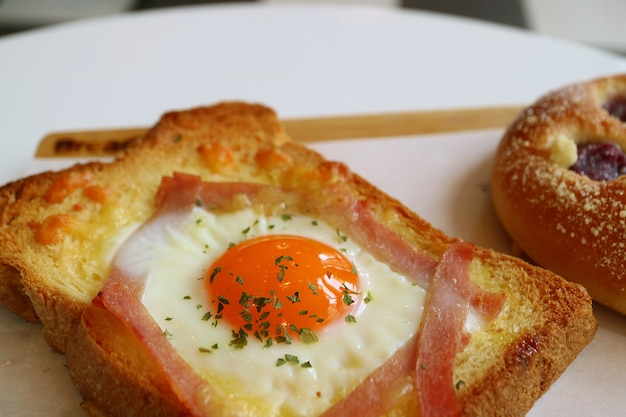 Zbliżenie świeże domowe francuskie tosty z jajkiem po stronie słonecznej na białym stole