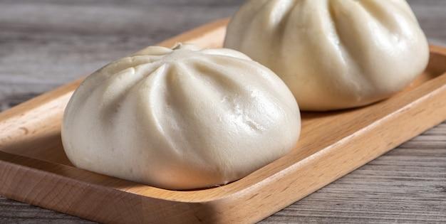 Zbliżenie świeżego baozi pyszne, chińska gotowana na parze bułka mięsna jest gotowa do spożycia na talerz służący i parowiec, z bliska, kopia koncepcja projektowania produktu przestrzeni.