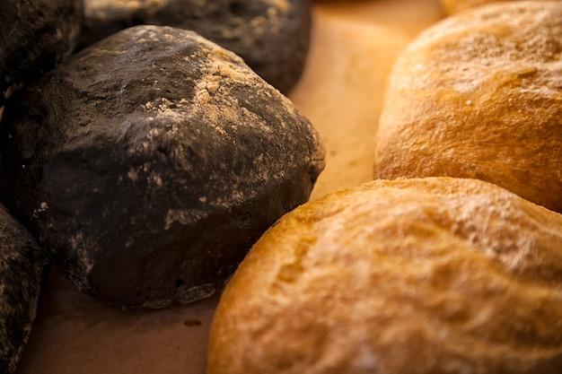 Zbliżenie świeżego białego chleba i czarnej ciabatty w bułkach w piekarni, świeże bochenki